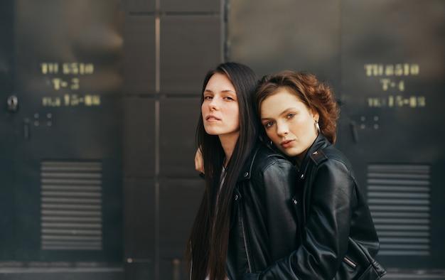 Portret van een paar meisjes in lederen jassen poseren