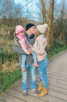 Portret van een paar met haar gelukkige dochtertje zoenen. familie liefde concept.
