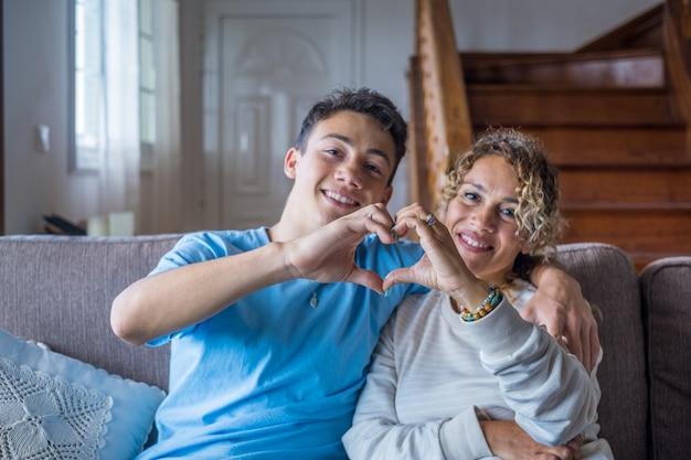 Portret van een paar moeder en zoon die samen een huis maken van een hartliefde met hun vingers en handen met de gezichten op de achtergrond. aanhankelijk tiener en vrouw genieten
