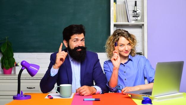 Portret van een paar universitaire studenten examen in college jonge mannelijke leraar met vrouwelijke student over