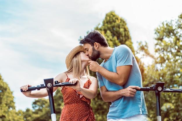 Portret van een paar verliefd kussen met behulp van elektrische scooter in het park