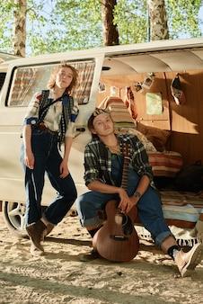 Portret van een paar wandelaars die poseren in de buurt van het busje dat ze samen gaan kamperen in het bos