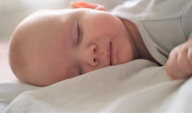Portret van een pasgeboren baby die op een witte deken slaapt.