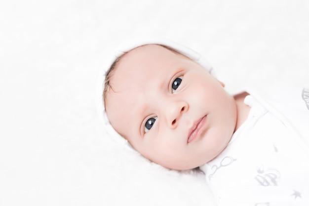 Portret van een pasgeboren babyjongen in een pet op een wit