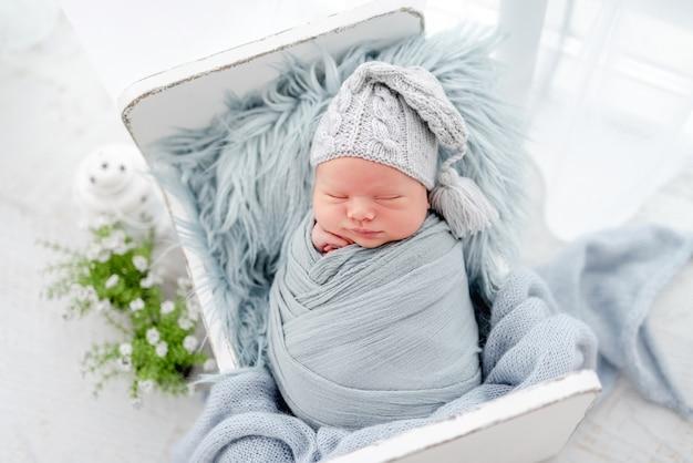 Portret van een pasgeboren babyjongen, ingebakerd in lichtblauwe stof en met een gebreide muts die zoet slaapt op een wit, klein ontworpen bed. schattig baby kind aan het dutten tijdens studio fotoshoot