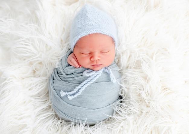 Portret van een pasgeboren babyjongen, ingebakerd in lichtblauwe stof en met een gebreide muts die zoet slaapt op een witte vacht. schattig baby kind dutten