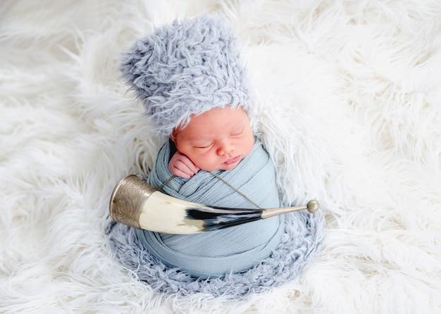 Portret van een pasgeboren babyjongen, ingebakerd in lichtblauwe stof en met een harige kaukasische hoed die in de studio slaapt. schattig baby kind dutten met traditionele hoorn