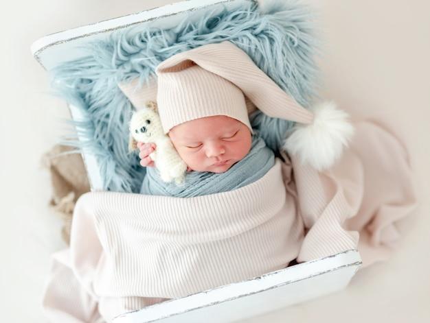 Portret van een pasgeboren babyjongen met een gebreide muts die op een wit, klein ontworpen bed onder de deken slaapt en speelgoed vasthoudt. schattig baby kind aan het dutten tijdens studio fotoshoot