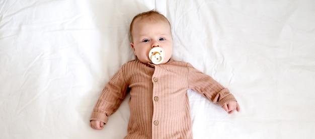 Portret van een pasgeboren babymeisje dat op een bed met een tepel fopspeen ligt
