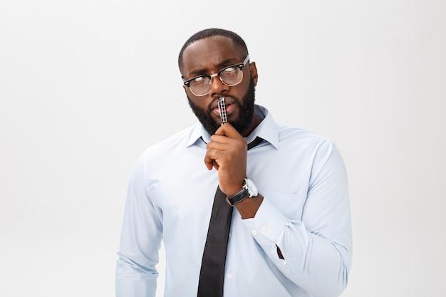 Portret van een peinzende afrikaanse amerikaanse zakenman in een grijs kostuum dat met pen op zijn hand denkt.