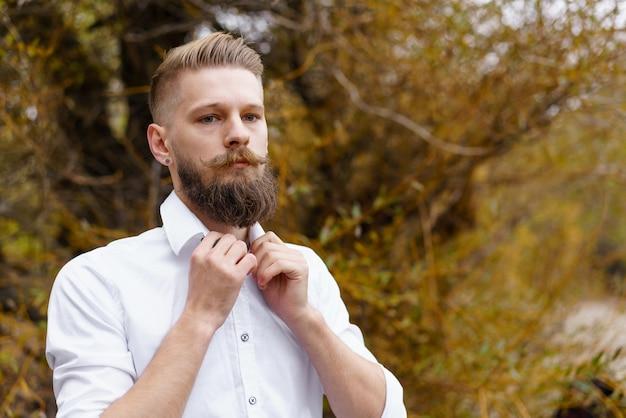 Portret van een peinzende, bebaarde, aantrekkelijke jonge man in een wit overhemd die uitkijkt over een herfstpark in oktober...