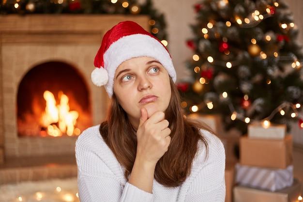 Portret van een peinzende droevige vrouw met een witte trui en een kerstmuts in een ingerichte woonkamer, wegkijkend, kin vasthoudend, denkend, kersttijd.
