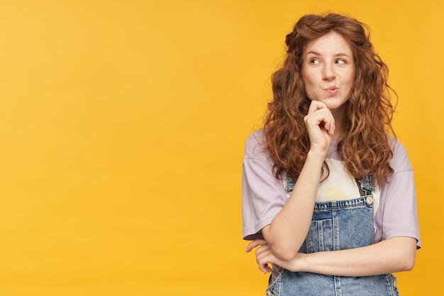 Portret van een peinzende jonge gembervrouw met lang golvend haar, kijkt bedachtzaam opzij naar de kopieerruimte, houdt haar kin vast en denkt na over de toekomst. geïsoleerd over gele muur