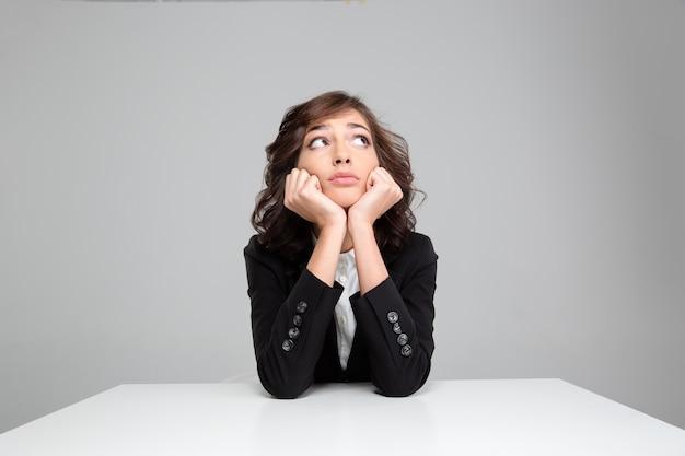 Portret van een peinzende jonge, vrij krullende vrouw in een zwarte jas die wegkijkt