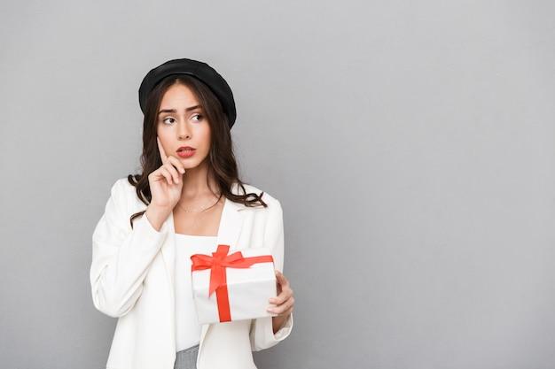 Portret van een peinzende jonge vrouw gekleed in jas over grijze achtergrond, met huidige doos, wegkijken