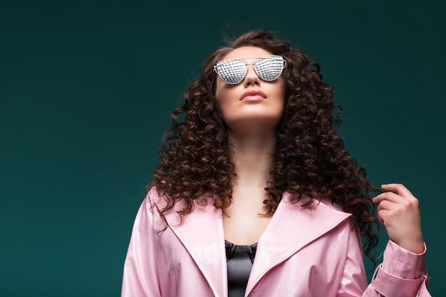 Portret van een peinzende meisje met krullend haar en zonnebril. kijkt omhoog en droomt.