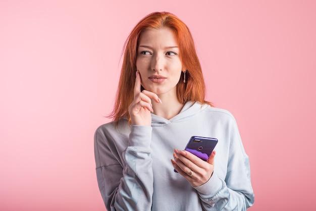 Portret van een peinzende roodharige meisje met een smartphone in haar handen in de studio op een roze achtergrond