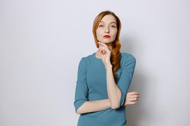 Portret van een peinzende roodharige vrouw in een blauwe jurk