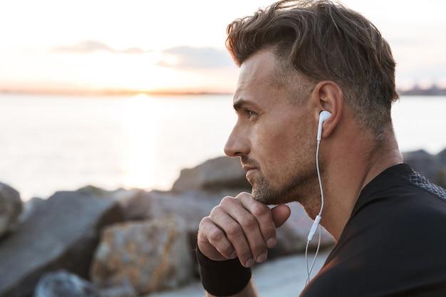 Portret van een peinzende sportman, luisteren naar muziek close-up