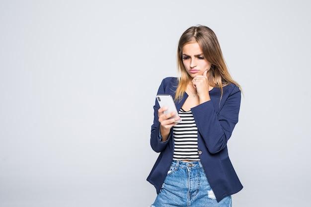 Portret van een peinzende vrouw die geïsoleerde mobiele telefoon met behulp van