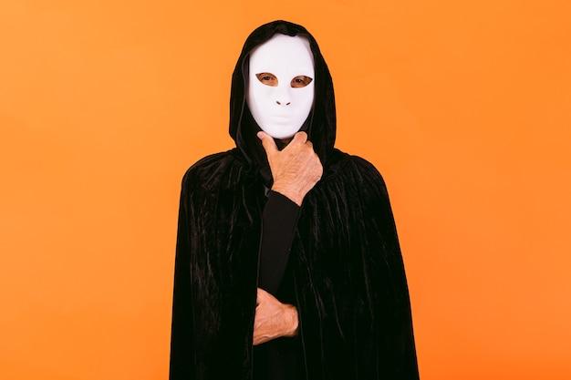 Portret van een persoon met een wit halloween-moordenaarsmasker, een cape en een capuchon die naar de camera kijkt, de kin met de hand aanraakt, gekleed voor halloween over een oranje achtergrond