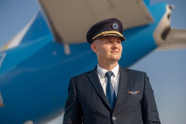 Portret van een piloot in uniform die wegkijkt, staande voor een groot passagiersvliegtuig klaar voor vertrek op de luchthaven. vliegtuigen, beroep, transportconcept