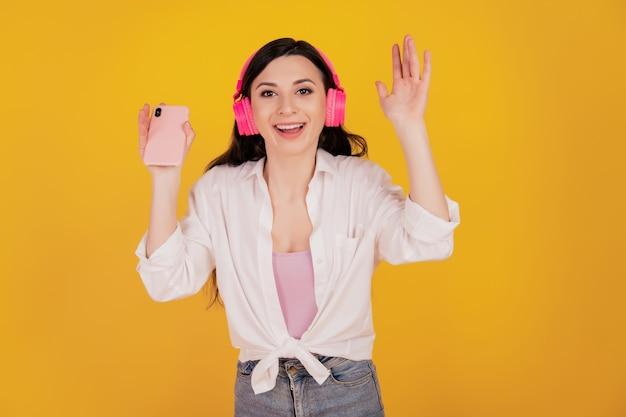 Portret van een positief charmant meisje dat een smartphone vasthoudt, een koptelefoon draagt, veel plezier op een gele achtergrond