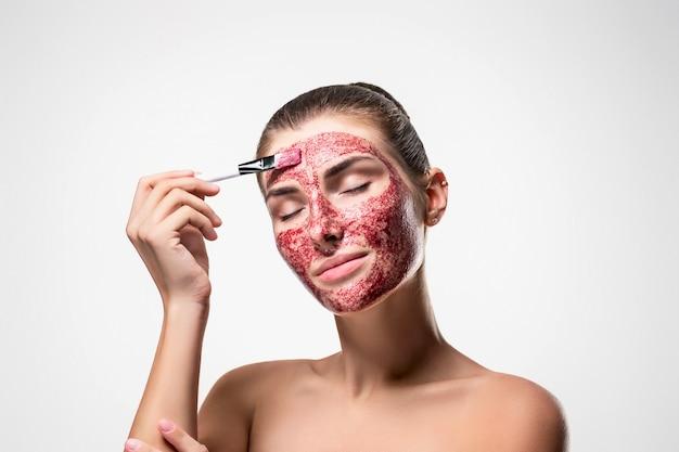 Portret van een positief en kalm meisje met een rood cosmetisch masker op haar gezicht.