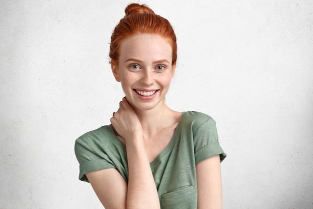 Portret van een positief gember jong vrouwelijk model dat tevreden is om gefotografeerd te worden, heeft een brede glimlach en witte tanden, vormt tegen een betonnen muur.