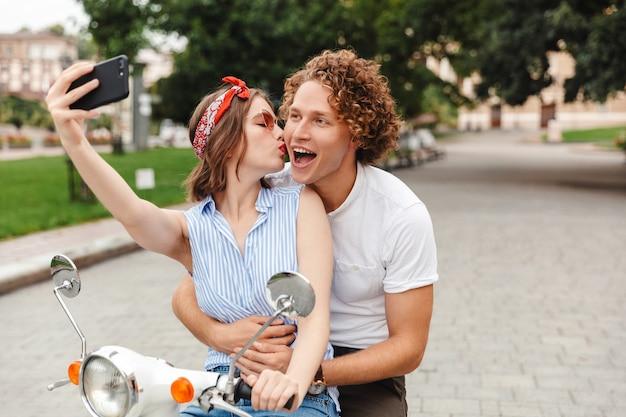 Portret van een positief jong koppel rijden op een motor samen in de stad straat, een selfie nemen