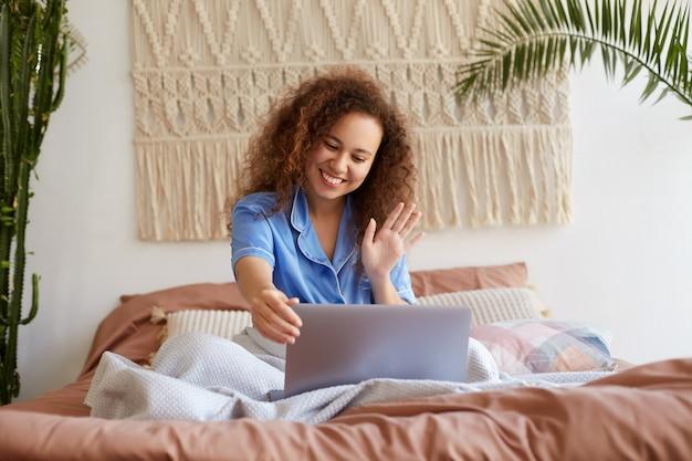 Portret van een positief jong krullend mulatmeisje dat in bed ligt, gekleed in blauwe pyjama's, breed glimlachend, naar een laptopmonitor kijkt en met zijn hand zwaait, zegt hallo tegen familieleden via videochat.
