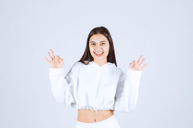 Portret van een positief jong meisje dat ok gebaar toont.