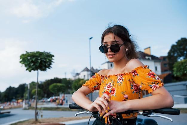 Portret van een positief jong meisje in een zonnebril die bij haar fiets staat.