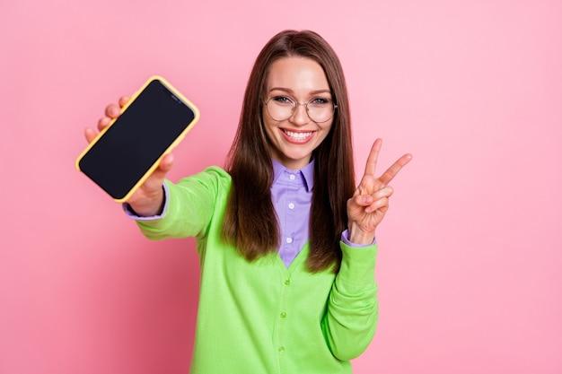 Portret van een positief meisje houdt een smartphone vast en maakt een v-teken geïsoleerd over pastelkleurige achtergrond