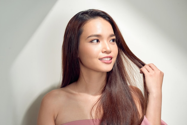 Portret van een positief meisje met een stralende witte glimlach die geniet van zonlicht en wegkijkt, geïsoleerd op een witte achtergrond