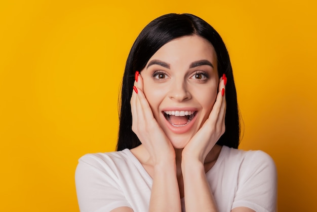 Portret van een positief meisje voelt zich opgewonden aanraking handen wangen nieuws verkoop geïsoleerd over gele kleur achtergrond
