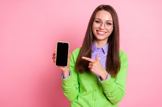 Portret van een positief meisje wijsvinger smartphone draagt groene kleding geïsoleerd over pastelkleurige achtergrond