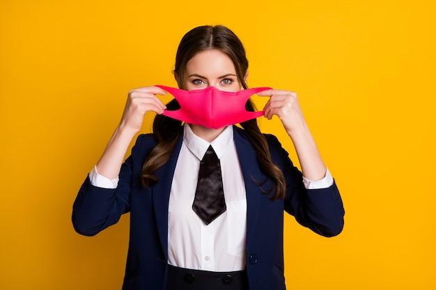 Portret van een positief middelbare schoolstudentmeisje draagt een rood medisch masker