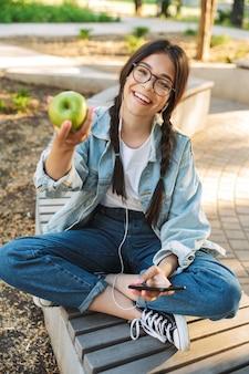 Portret van een positief vrolijk jong studentenmeisje met een bril die buiten op een bankje zit in het natuurpark met behulp van een mobiele telefoon die luistert naar muziek met een koptelefoon die een appel vasthoudt.