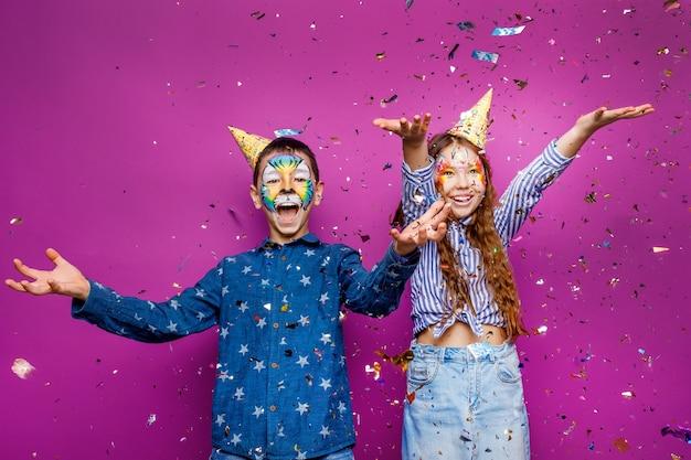Portret van een positief vrolijk klein meisje en jongen, veel plezier geïsoleerd over een violetkleurige muur die serpentine vliegt