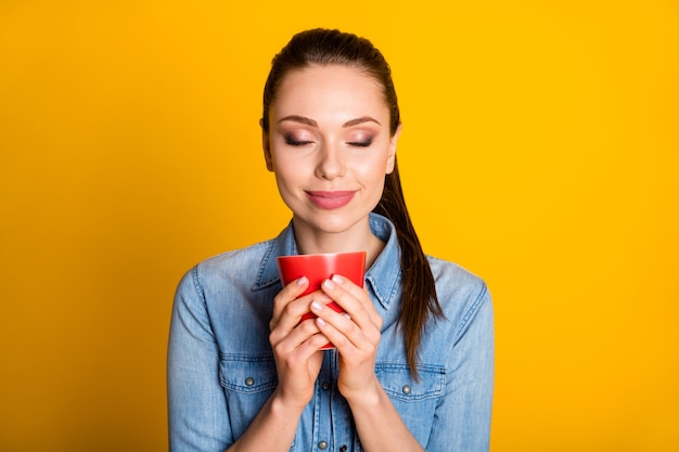 Portret van een positief vrolijk meisje dat hete cappuccino-kopgeur vasthoudt, geniet van het dragen van een goed uitziende stemmingsoutfit geïsoleerd over een heldere glanskleurachtergrond