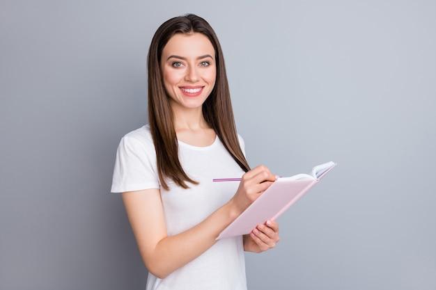 Portret van een positief vrolijk meisje dat thuis studeert, schrijfboek schrijft