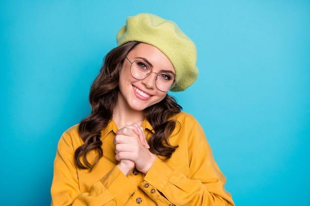 Portret van een positief, vrolijk meisje geniet ervan, voel me dankbaar, draag een goed uitziende outfit geïsoleerd over een blauwe kleurachtergrond
