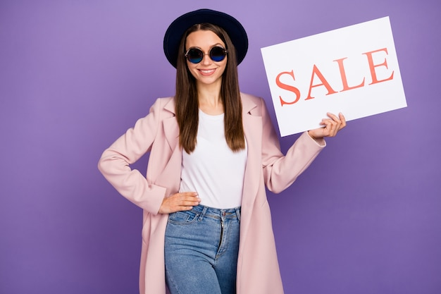 Portret van een positief vrolijk meisje houdt wit papier vast met woordverkoop beveel boetiekkoopjes aan, draag pastel bovenkleding denim geïsoleerd over violette kleur achtergrond