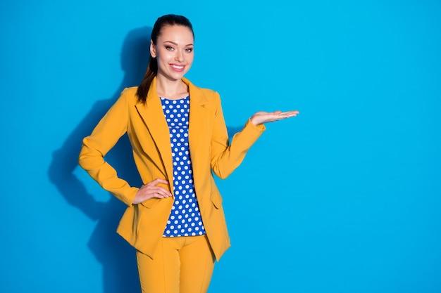 Portret van een positief vrolijk meisje, uitvoerend vertegenwoordiger, promotor, houd de hand vast, raad aan om geselecteerde advertenties aan te bevelen, draag een gele blazerbroek geïsoleerd over een blauwe achtergrondkleur