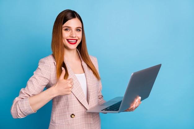 Portret van een positief zelfverzekerd meisje dat een laptop vasthoudt en een duim omhoog tekent