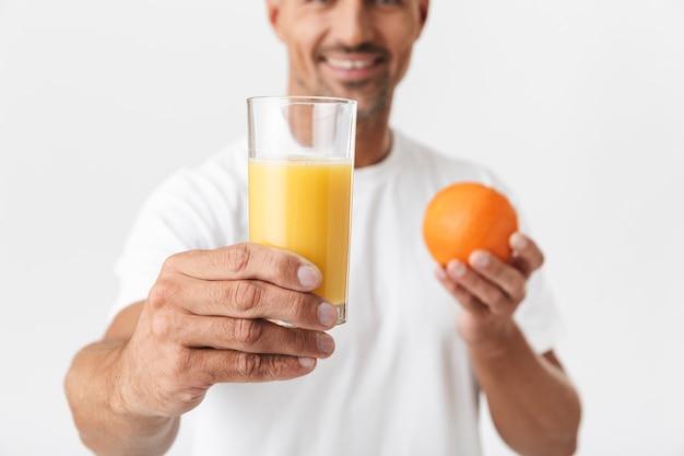 Portret van een positieve 30-jarige man met haren in een casual t-shirt met een glas sap en sinaasappelfruit op wit wordt geïsoleerd