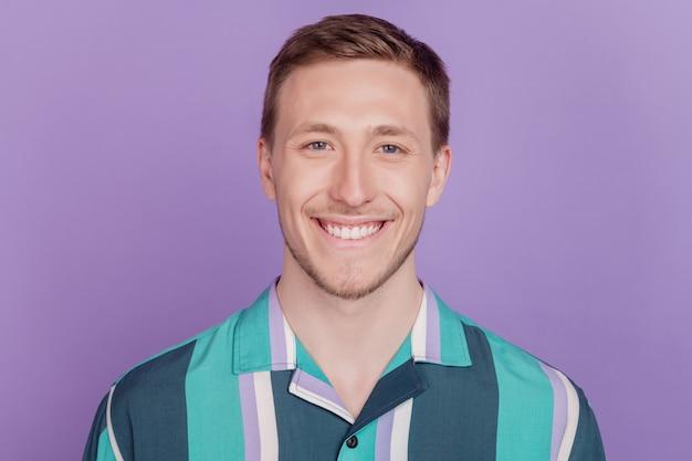 Portret van een positieve, aardige, aantrekkelijke kerel met een stralende glimlach op een violette achtergrond