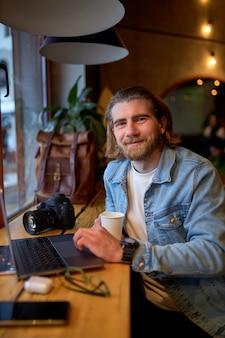 Portret van een positieve bebaarde man die naar de camera kijkt terwijl hij op een laptop in café werkt