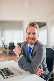 Portret van een positieve gemberzakenman, die bij camera glimlacht.